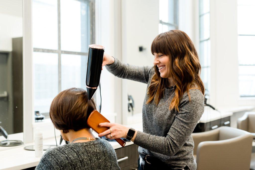 kampaaja kuivaamassa asiakkaansa hiuksia