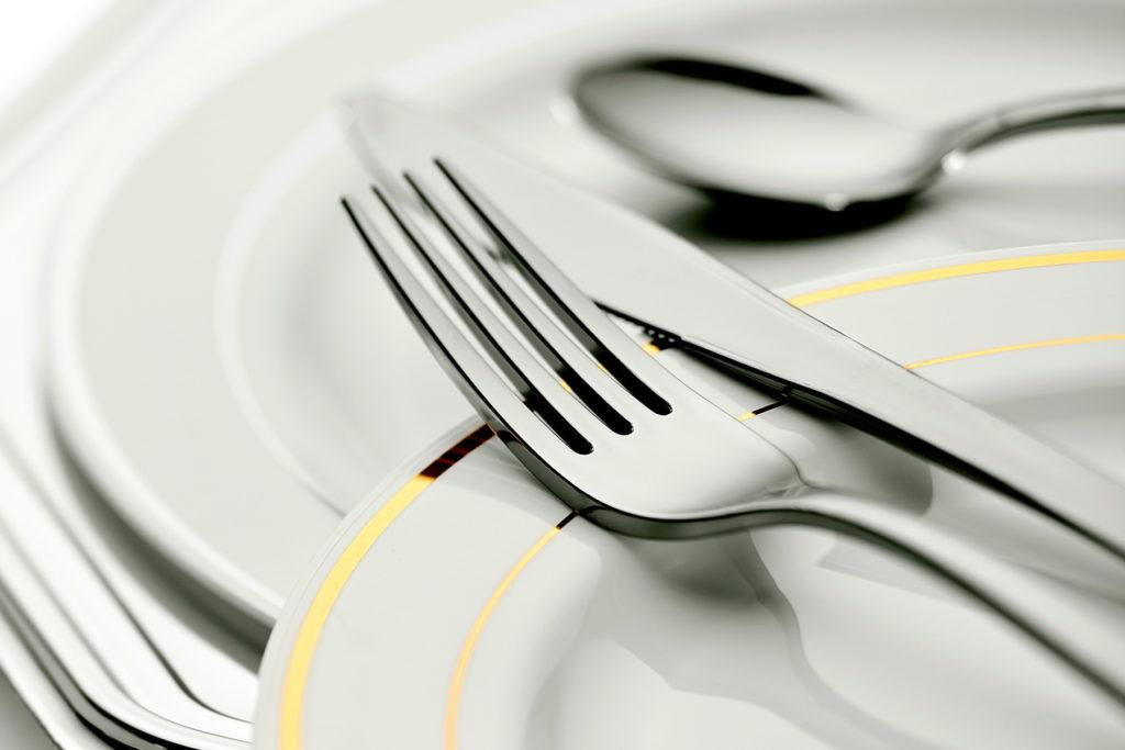 Haarukka, veitsi ja lusikka valkoisten lautasten päällä.