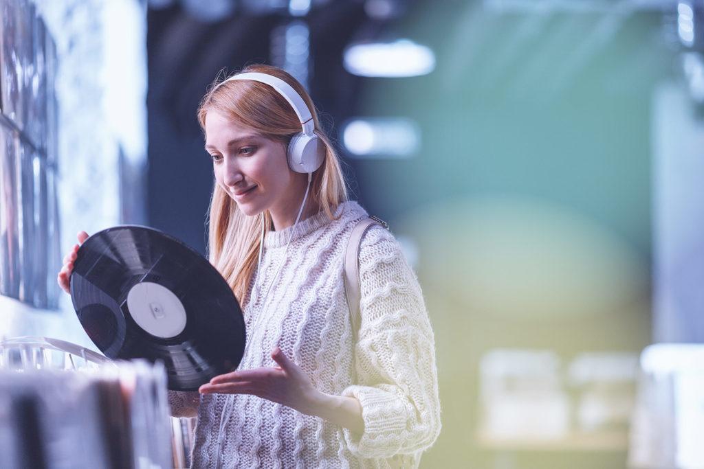 Musiikkia kuunteleva tyttö levykaupassa