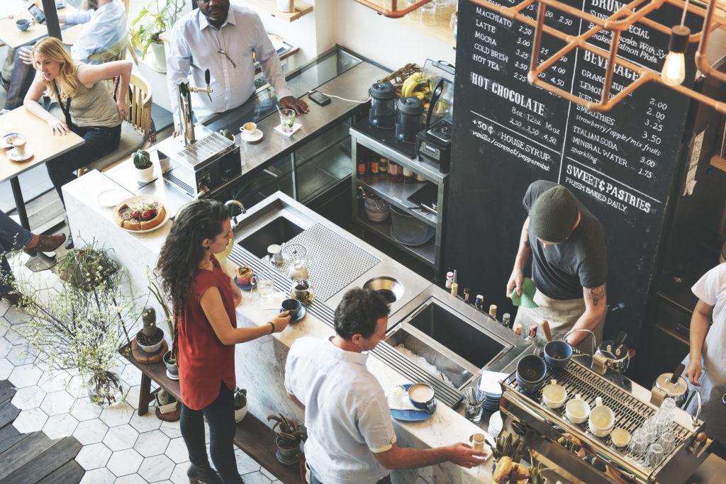 ihmisiä kahvilan tiskillä