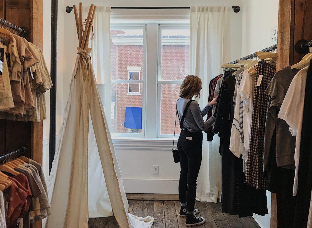 nainen selaa vaatteita vaatekaupassa