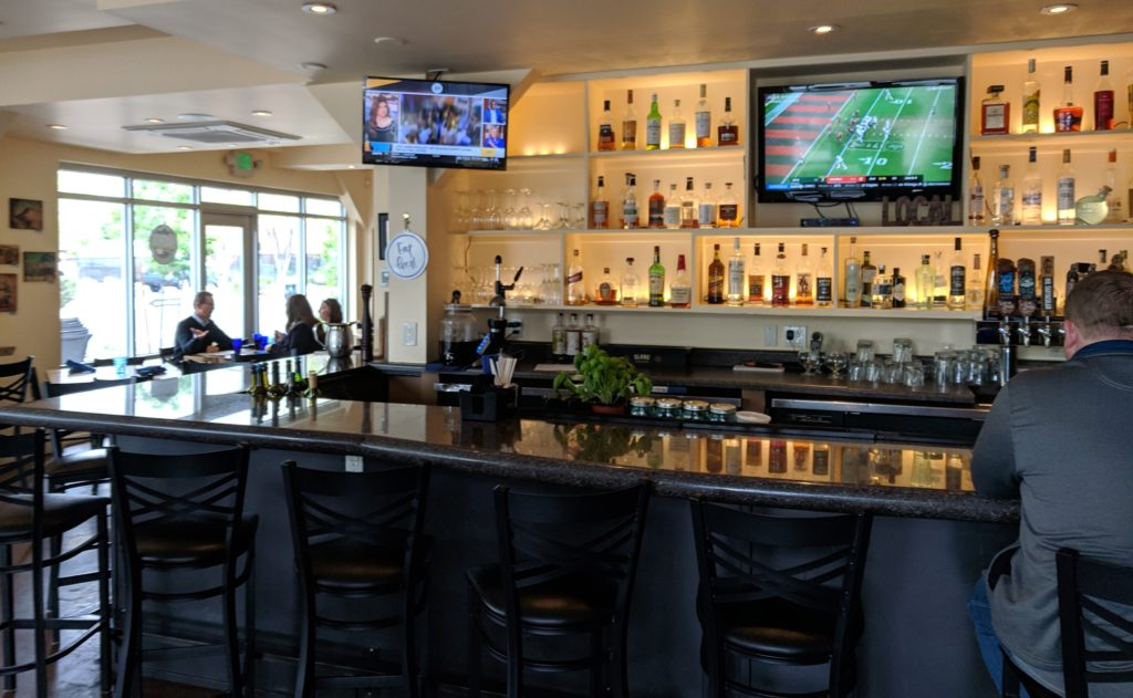 baari, jossa tv auki ja mies istuu baaritiskillä