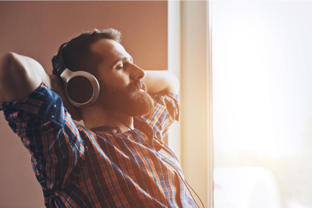 parrakas mies nauttii musiikista kuulokkeet korvilla