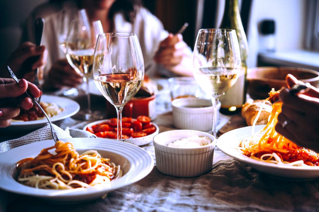Kolme henkilöä syövät pastaa ravintolassa.