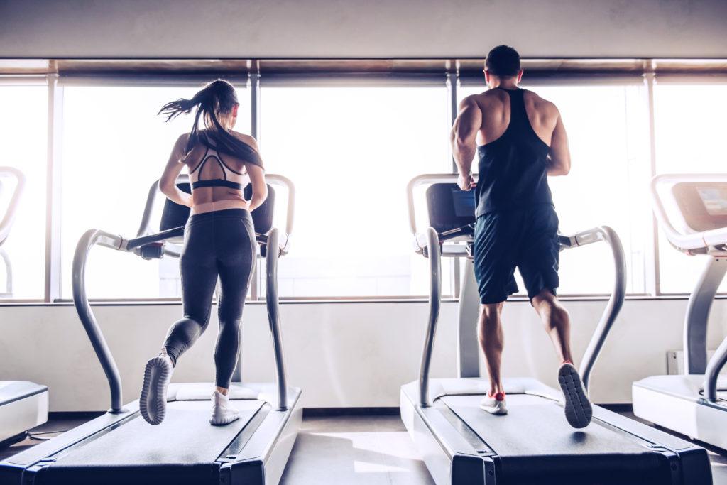 Nainen ja mies juoksevat vierekkäisillä juoksumatoilla kuntosalilla.