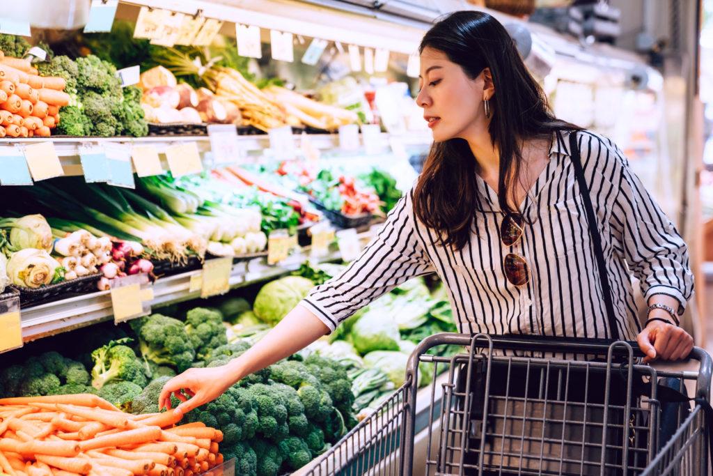 Nainen ruokakaupassa vihannesosastolla