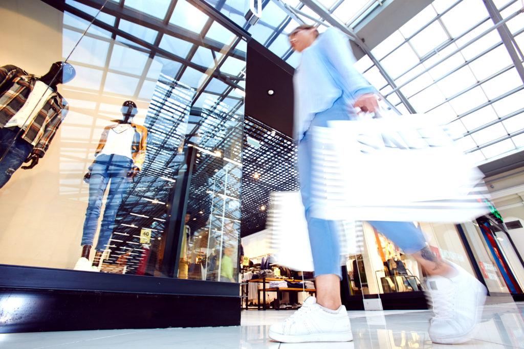 Nainen kävelee kauppakeskuksessa ostoskassien kanssa