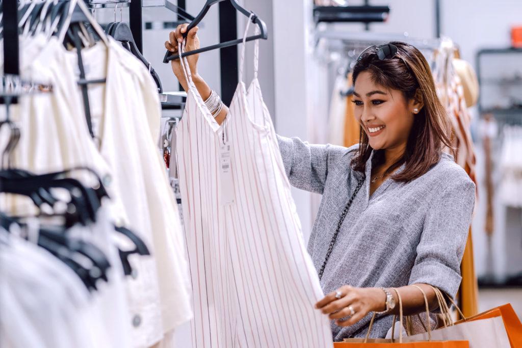 Nainen shoppailemassa vaatekaupassa.