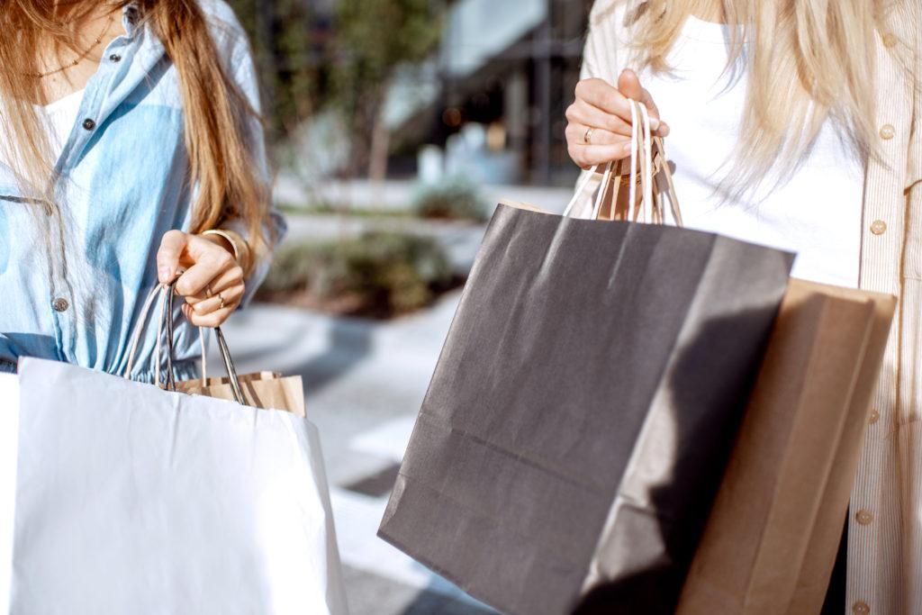 Kaksi naista ostoskassit käsissään ulkona
