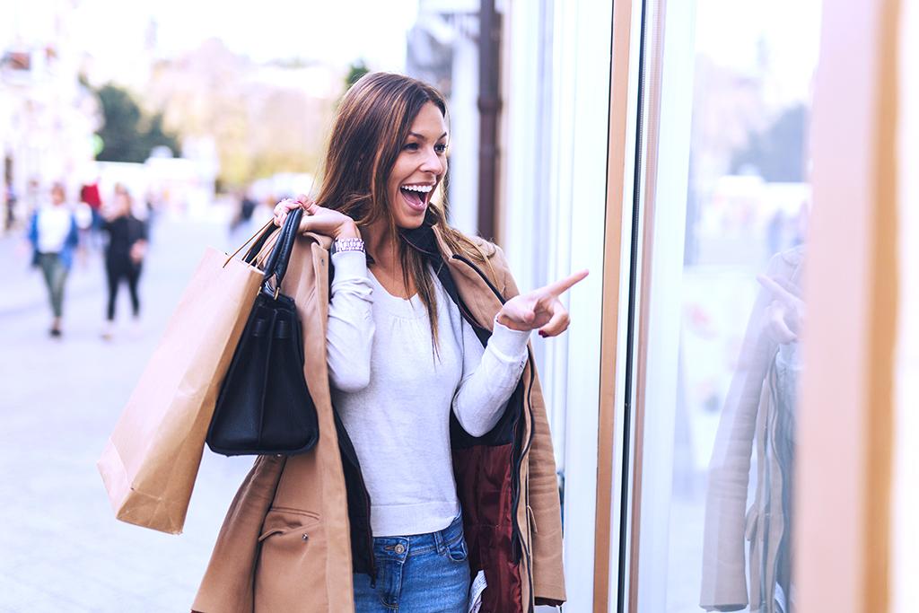 Nainen ostoskassien kanssa myymälän edessä tuotteita osoittaen