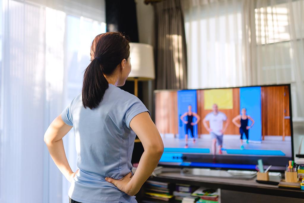 Nainen jumppaa olohuoneessa osallistuen striimatulle liikuntatunnille etänä kotona
