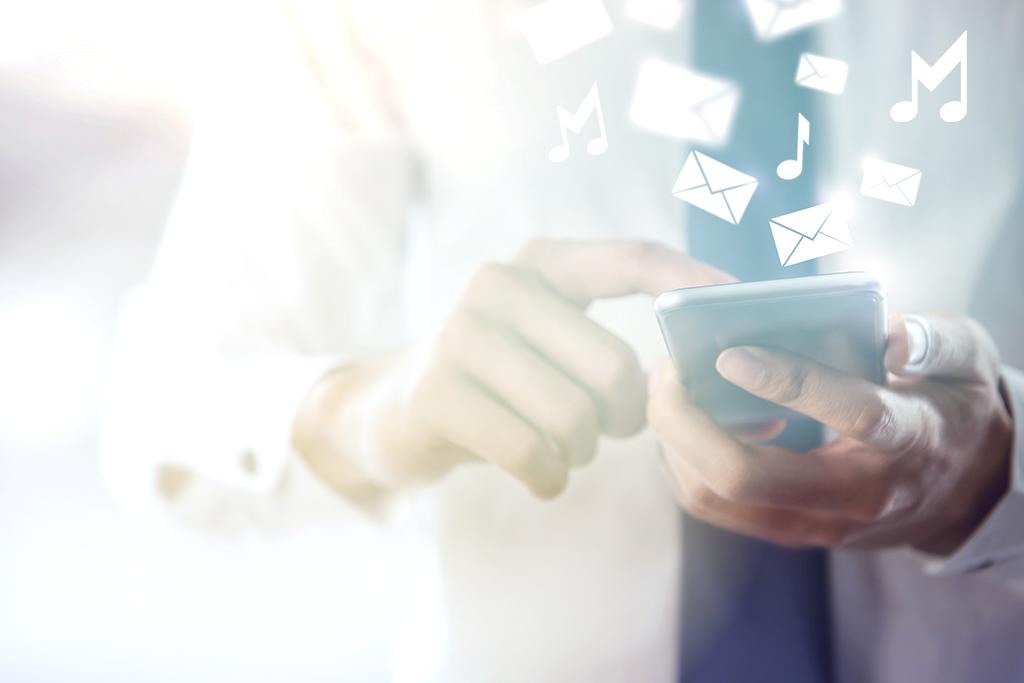 Miehen kädessä puhelin ja sen yllä kuvakkeita viesteistä sekä nuoteista